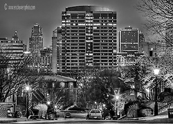 The Union Hill neighborhood of KCMO in the early morning right before a dreary sunrise. A view of Crown Center is off in the distance, then beyond that, the skyline of downtown Kansas City.