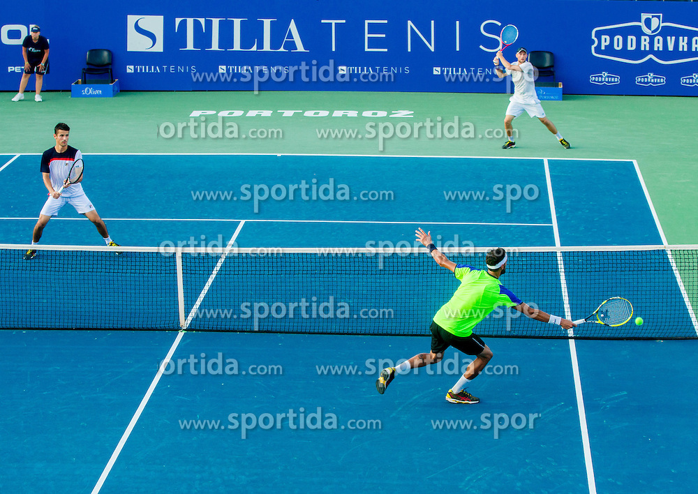 Matjaz Jurman of Slovenia (yellow) in doubles against Mike Urbanija and Tom Kocevar-Desman of Slovenia during Day 1 of ATP Challenger Tilia Slovenia Open 2014 on July 7, 2014 in  Tennis stadium SRC Marina, Portoroz / Portorose, Slovenia. Photo by Vid Ponikvar / Sportida