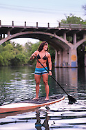 A woman enjoys stand up paddle boarding near Barton Springs in Austin, Texas.