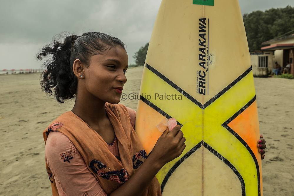 Putting wax on their boards. The girls are getting ready for surfing at Cox's Bazar's beach, Bangladesh