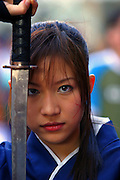 Thailand, Bangkok, portrait of young thai woman in traditional dress with a sword