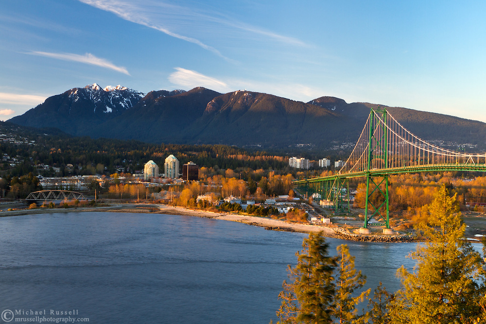 Sunset light falls on the Lions Gate Bridge with North Vancouver, West Vancouver and the Coast Mountains in the background.