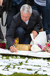 Parliament Square, Westminster, London, June 17th 2016. Following the murder of Jo Cox MP friends and members of the public lay flowers, light candles and leave notes of condolence and love in Parliament Square, opposite the House of Commons. PICTURED: A man writes a message of condolence.