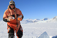 Marine chemist Melissa Chierici (Institute of Marine Research) carries samples of glacial ice collected from lonely chunk sitting atop frozen fjord; Kongsfjord, Svalbard, Norway.