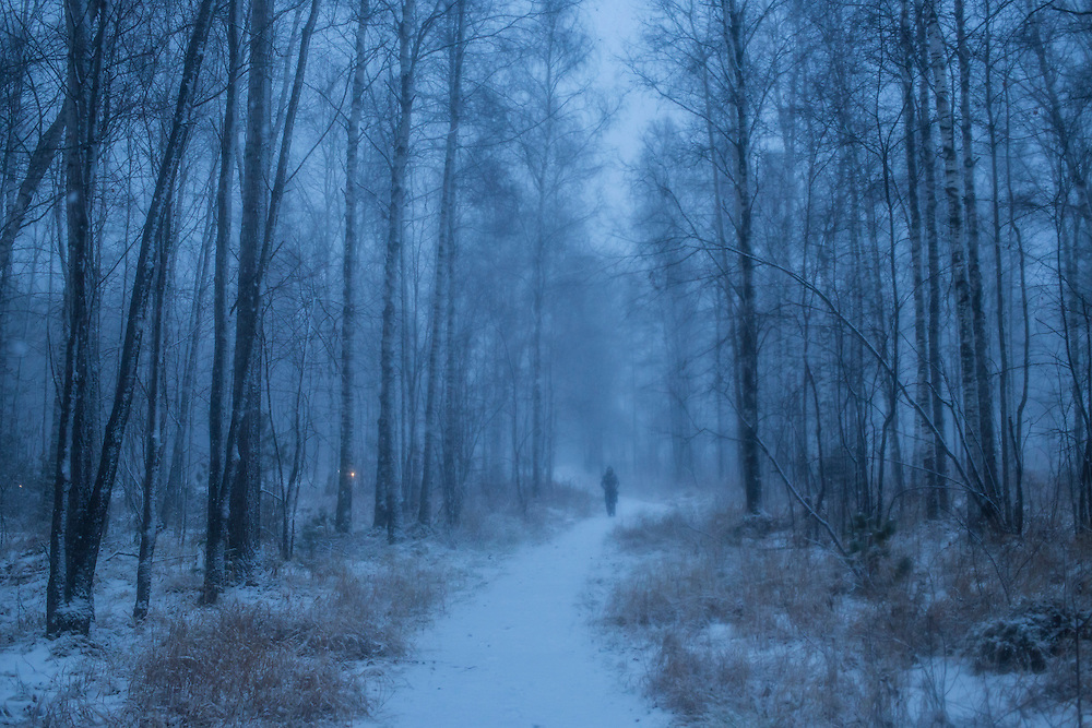 A man walks through the forrest as snow falls on Sunday, October 20, 2013 in Baikalsk, Russia.