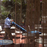 """Makay  a sudanese refugee carries a deckchair as he he set up the pool area for the customers at the Royal Beach Hotel on February 28 2011. The municipality hung 1,500 red flags around the city as a sign of warning and put up hundreds of banners reading: """"Protecting our home, the residents of Eilat are drawing the line on infiltration."""" Eilat Mayor Meir Yitzhak Halevi said that 10 percent of the city's population was currently made up of migrants and that the residents feel that the city has been conquered...Photo by Olivier Fitoussi."""