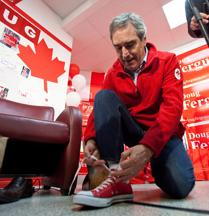 Liberal leader Michael Ignatieff ties up some new red converse shoes for the last days at the campaign during a campaign stop in London, Ontario, Friday April 29, 2011.<br /> REUTERS/Geoff Robins (CANADA)