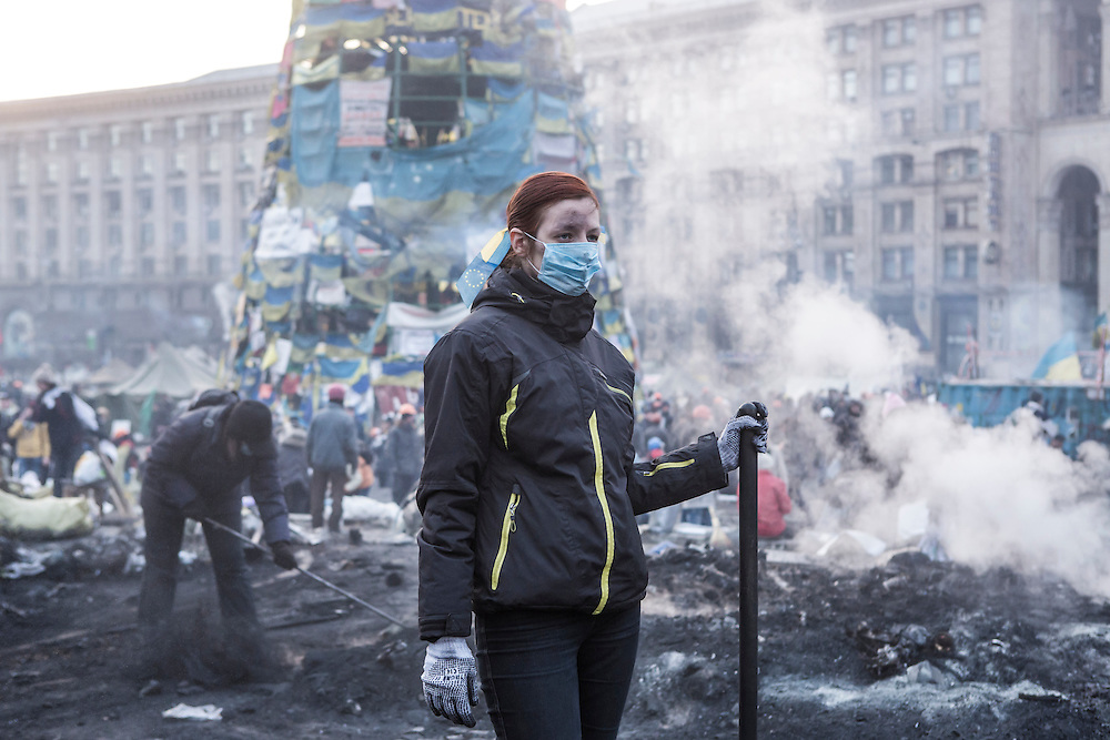 KIEV, UKRAINE - FEBRUARY 20: A woman clears ashes and debris with other anti-government protesters from a newly-occupied portion of Independence Square on February 20, 2014 in Kiev, Ukraine. After several weeks of calm, violence has again flared between anti-government protesters and police, with dozens killed. (Photo by Brendan Hoffman/Getty Images) *** Local Caption ***