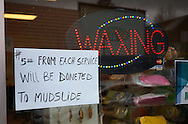 A sign referring to mudslide victims is seen at a beauty shop in downtown Arlington, Washington March 28, 2014.  Rescue officials said the death toll from a catastrophic mudslide in Washington state is soon expected to climb far higher, as some residents voiced anger that they were prevented from helping in the initial disaster response six days ago.   REUTERS/Rick Wilking (UNITED STATES)