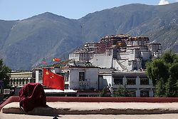 A file photo made available on 21 September 2016 of of a Tibetan monk covering himself with his robes to avoid being photographed with the Potala Palace in the background on the roof of the Jokhang Temple in Lhasa, Tibet Autonomous Region, China, 10 September 2016. The famous Potala Palace used to be the main residence of the Dalai Lama but is now a preserved as a museum and world heritage site.
