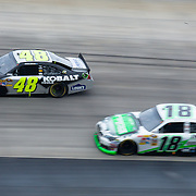 Jimmie Johnson #48 of the Lowe's/Kobalt Tools team pass Kyle Busch #18 near turn three during Sprint Cup Series Sunday, Oct. 02, 2011 at Dover International Speedway in Dover Delaware.