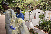 The Red Cross is undertaking safe and dignified burials in all Ebola-affected countries, ensuring that those who have died from the disease are treated with respect, while also ensuring the safety of communities. This is critical work, often performed by volunteers, and undertaken at the most dangerous time.<br /> <br /> Volunteers must wear full personal protective equipment and work in teams of seven. Seen here is a team who is carrying the body of a 40 year-old woman who died from Ebola virus and has been transported from Donka Hospital to the Conakry Cemetary to be buried. The team is getting ready to transport the body from the truck to the grave.  UNMEER/Martine perret. 16 January 2015