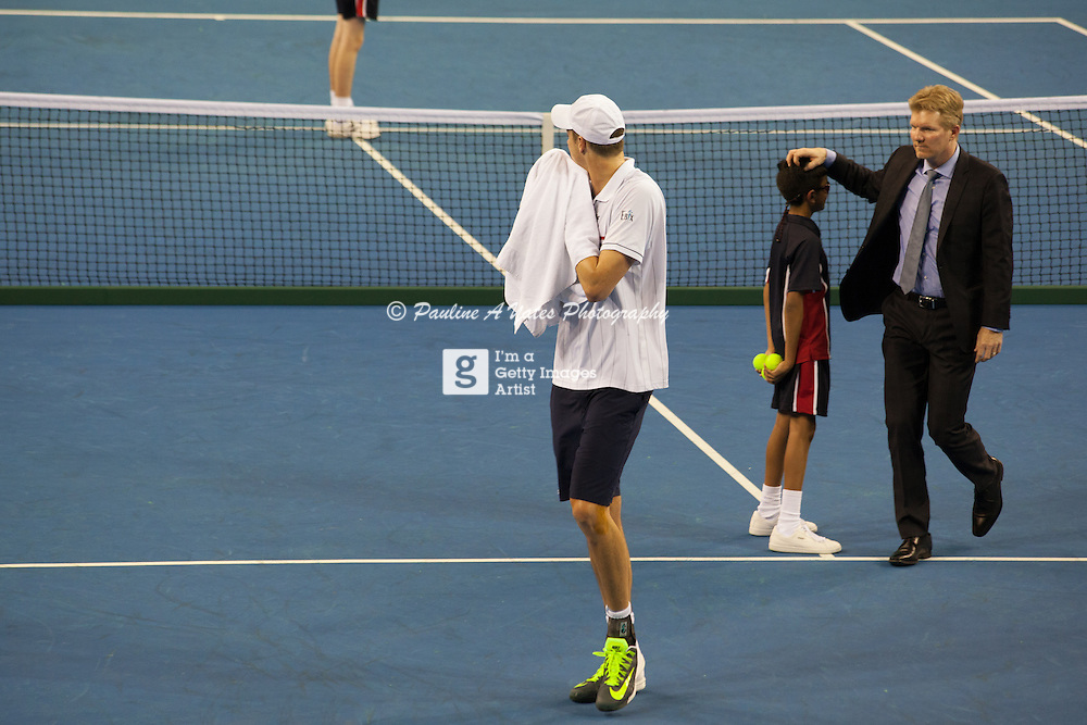 Jim Courier thanks a ball-kid as John Isner leaves the court following the USA's defeat by GB in the Davis Cup.