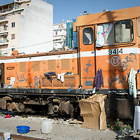A disused train engine is now home to migrants from around the world, as they attempt to smuggle themselves out of Greece from the port of Patras.