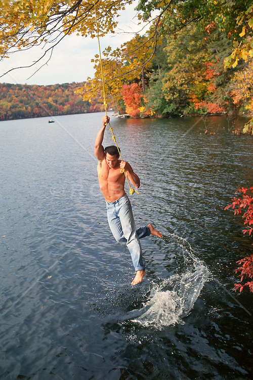 Shirtless young man swinging on a rope over the shore of the Hudson River