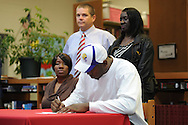 Lafayette High's Jeremy Liggins (1), with his mother LaTisha Liggins (sitting), former Lafayette High coach Anthony Hart (standing left) and Linda Liggins, signs a National Letter of Intent to play football at LSU, in Oxford, Miss. on Wednesday, February 1, 2012.