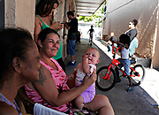 MELISSA LYTTLE | Times<br /> While activity swirls around a busy hallway, neighbor Fletter Harris, left, sits with Michelle White as she bounces her her 5-month-old granddaughter Angel Kelee White on her knee, while her daughter Keisha Grooms checks her phone at the Mosley Motel. Harris has lived at the Mosley on and off for 8 years, and White, her fianc&eacute;, daughter and granddaughter moved in about six weeks ago, after leaving a motel in Clearwater after her fianc&eacute; lost his job. &quot;We need some help because there's not enough low-income family housing around here,&quot; said Michelle White. &quot;And this ain't no place to raise kids.&quot;