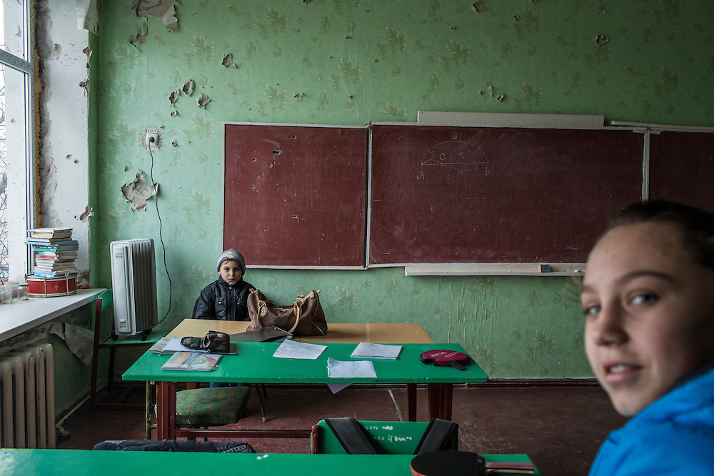 Students in a classroom damaged by shelling on Friday, December 11, 2015 in Troitske, Ukraine.