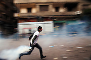 An Egyptian protestor runs to throw clear a tear gas canister fired by nearby security forces during street battles November 21, 2011 near Tahrir square  in central Cairo, Egypt. Thousands of protestors demanding the military cede power to a civilian government authority clashed with Egyptian security forces for a third straight day in Cairo, with hundreds injured and at least 24 protestors killed.  (Photo by Scott Nelson)