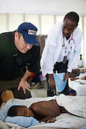Jason Harris, left, a pediatric infectious disease specialist volunteering with Project HOPE, examines a young cholera patient with a staff doctor at the Hospital Albert Schweitzer on Saturday, October 30, 2010 in Deschapelles, Haiti.
