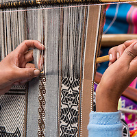 Peru, Cusco Region, Woman weaving using traditional loom outside gift shop at Ccochahuasi Animal Sanctuary in Sacred Valley