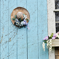 Closeup of picturesque Cape Cod barn door with flowering window box and decorated straw hat on door.