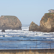 The Pacific Ocean erodes sea stacks from the rocky coast at Cleone, north of Mendocino, California, USA. A lone house sits on an isolated headland above pounding surf.
