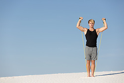 good looking athletic man working exercising on a sand dune in White Sands, NM