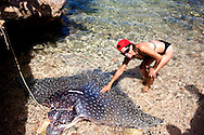 Woman and ray in Bariay, Holguin, Cuba.