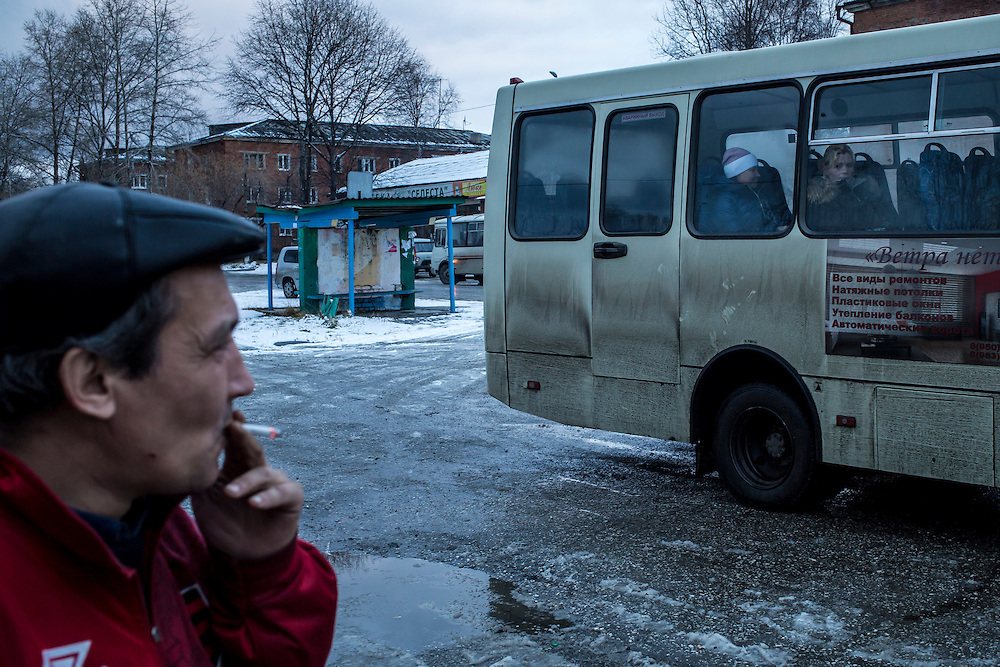 A man waits for a bus on Saturday, October 26, 2013 in Baikalsk, Russia.