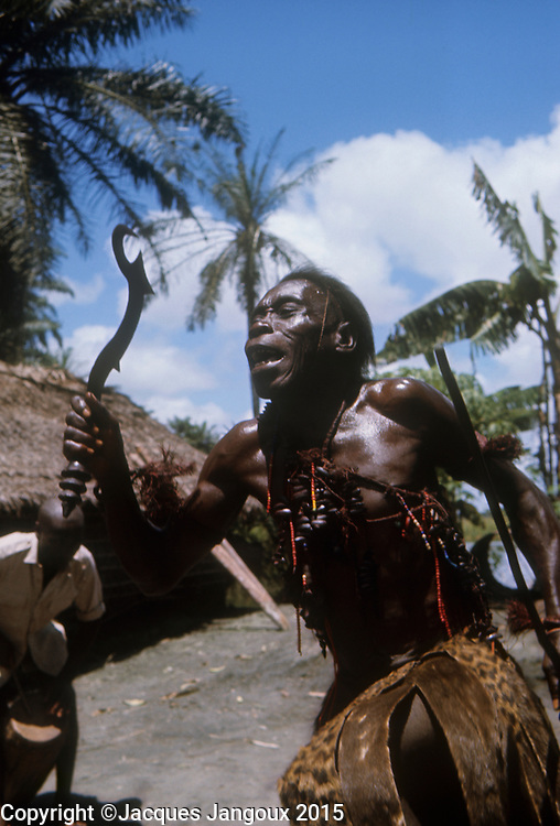 Africa, Democratic Republic of the Congo, Ngiri River area, Libinza tribe. Diviner dancing, holding ceremonial knife.