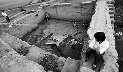 Chinese archaeologists and villagers work on an archaeological site of an ancient burial grounds thought to be dated 5,000 to 7,000 years ago in Xichuan county of Henan Province in China on 28 June 2010. China hasten to save its cultural and heritage relics that would be affected by the colossal  South-to-North Water Transfer project upon its completion. In Xichuan county alone, which used to the ancient city of Chu in 1063 B.C., 161 archaeological sites have been marked as cultural heritage points to be salvaged before they are submerged water from the Danjiangkou Dam reservoir by 2014.  The South-to-North Water Transfer project, the largest known water diversion project, was conceived in 1952 to solve the country's chronic water shortages and involves creating three routes to channel 44.8 billion cu m of water from southern China to the northern areas. As part of the project's central route, affecting Henan and Hubei provinces, water from the Danjiangkou reservoir will be diverted to Beijing. Parts of Xichuan county, a remote, mountainous region inaccessible by railway and home to 162,000 migrants, the most anywhere, will be completely submerged by water from the Danjiangkou reservoir by 2014. The vast resettlement of affected residents in Xichuan county began in August 2009 and lasted till 2011.