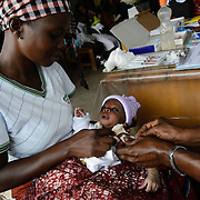 A baby in her mother's arms being vaccinated against tetanus at a health centre in Guiglo in western Cote d'Ivoire on 13 August 2012.