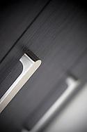 kitchen interior detail of metal handles on black drawer