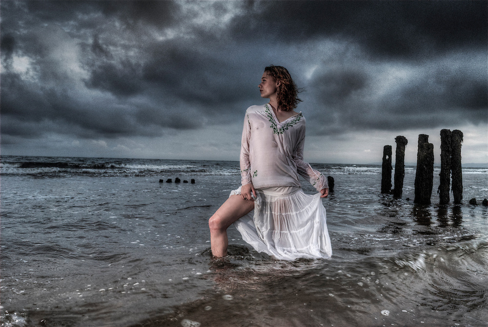 A statuesque girl in a white dress stands in the sea gazing into the distance as storm clouds gather.