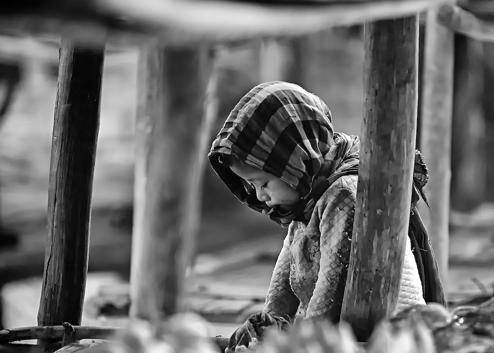 A Khamu boy stays cool under the benches of a roadside market stall near Luang Prabang, Laos.