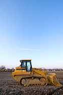A tracked loader rests in a muddy field near Joliet, IL.