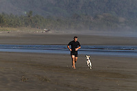 Man and dog running at the beach an early morning in Cost Rica
