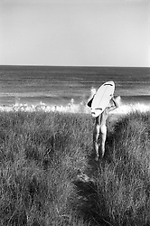 Man walking nude toward the beach with his surfboard