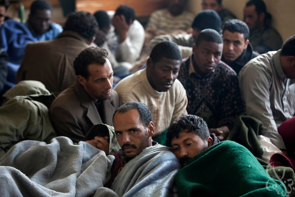 Dual nationality Libyans and some foreign men are detained in a makeshift jail inside a secondary school February 23, 2011in the eastern Libyan town of Shahat.  Nearly 200 men were being held, who according to opposition fighters were caught fighting alongside government forces. Amongst them were a few men from sub-Saharan Africa who opposition forces claim were mercenaries. .Slug: Libya.Credit: Scott Nelson for the New York Times