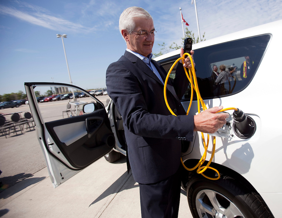 Toyota Motor Manufacturing Canada Chairman Ray Tanguay demonstrates how to charge the company's RAV4 EV electric vehicle August 5, 2011, which they announced will be assembled at the company's assembly plant in Woodstock, Ontario, Canada, starting in 2012.<br /> REUTERS/GEOFF ROBINS(CANADA)