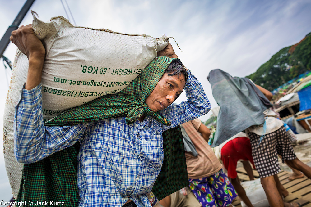 """10 JUNE 2014 - YANGON, MYANMAR:   Stevedores offload 110 pound (50 kilo) sacks of fish meal from a river freighter on the banana jetty. The """"banana jetty"""" is on the Yangon River north of central Yangon on Strand Road. Bananas, coconuts and other fruit are brought in here from upcountry, sold and reshipped to other parts of Myanmar (Burma). All of the labor here is done by hand. Porters carry the produce to the jetty and porters load the boats before they steam upriver.   PHOTO BY JACK KURTZ"""