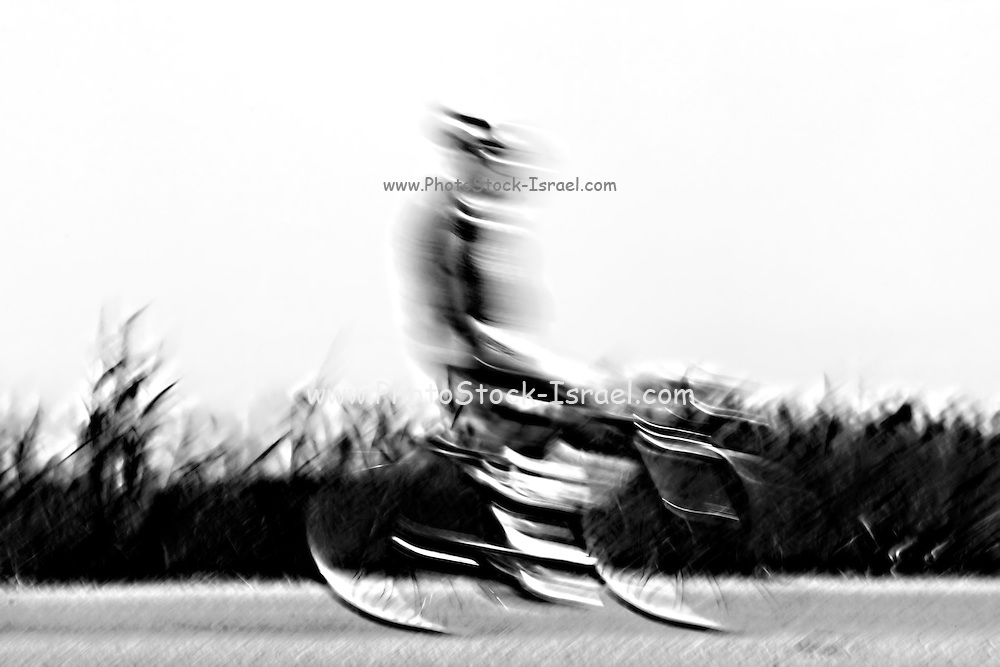 Motion blur of a bicycle rider in black and white
