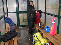 Cyclist is hiding from bad weather in a bus shelter..............
