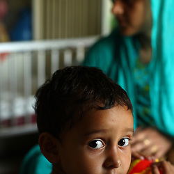 Hajra Bibi, 2, sits with her mother while her little sister recovers from bronchial pneumonia inside the Children's Hospital at the Pakistan Institute of Medical Sciences, P.I.M.S., in Islamabad, Pakistan on Sept. 18, 2007.