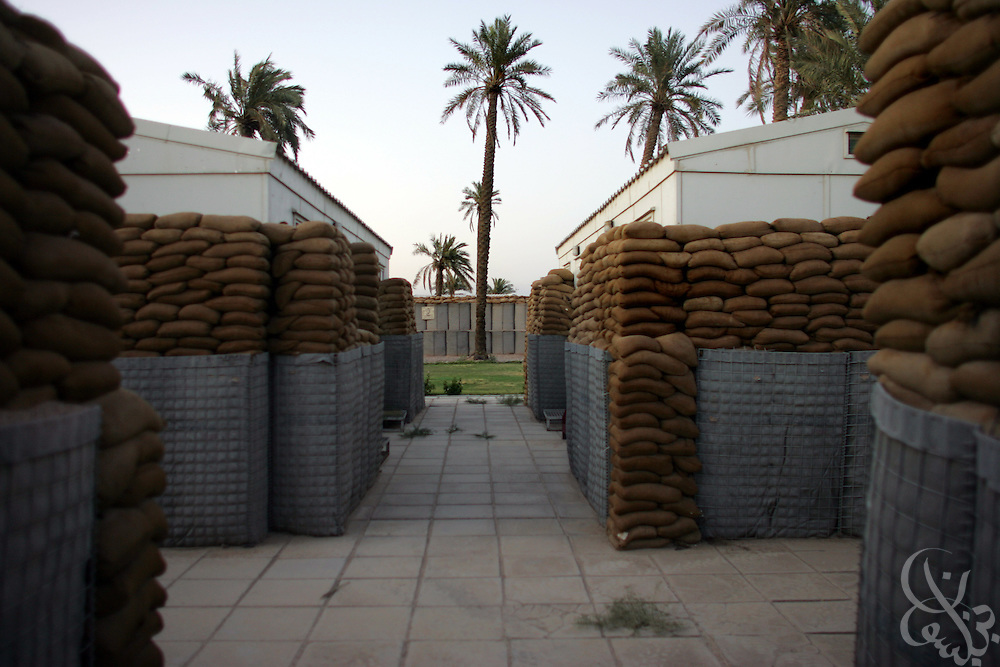 Private contractor housing trailers are fortified by sand bags and dirt filled barriers at a base in Basra, Iraq May 31, 2006.