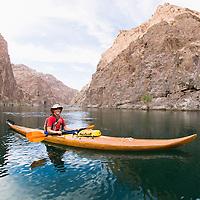 Kayaker navigates the Colorado River in his handmade wooden boat through The Black Canyon, Nevada.