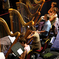 UK. London. Conductor, Sir Simon Rattle, during rehersals of Wagner's Das Rheingold, which, together with the Orchestra of The Age of Enlightenment, launch the Proms' first ever Ring Cycle as part of the BBC's Proms, in London's Royal Albert Hall..Photo shows Harpists..