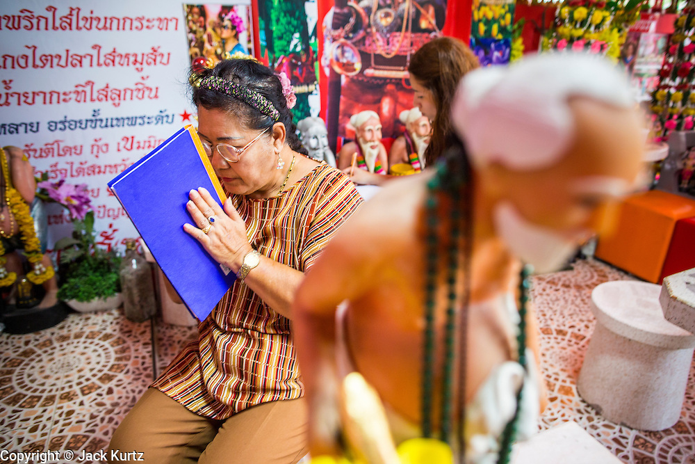 "03 MARCH 2013 - BANGKOK, THAILAND: A statue of Chuchok in front of a woman praying at the Chuchok Shrine after writing her prayers in a notebook. The Chuchok Shrine is in suburban Bangkok. More than 100 people a week come to the shrine to pray for good fortune or good health. People whose prayers are answered return to the shrine with ""coyote dancers"" to make merit and thank Chuchok. Coyote dancing is a Thai phenomenon created after the US movie ""Coyote Ugly"" where attractive young women dance in a sexually suggestive way, usually for pay. They're common at bars and festivals. Coyote dancers are typically better paid than other Thai women in the hospitality industry and usually are not allowed to date or see customers are off the dance floor. Coyote dancers perform at the Chuchok shrine because according to Buddhist literature Chuchok was a relatively repulsive old hermit and Brahmin priest who was cared for by a young woman after he made her family's wishes come true.   PHOTO BY JACK KURTZ"