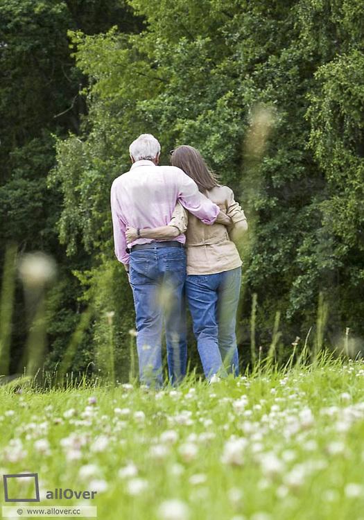 Seniorenpaar beim Spazierengehen an Waldrand, von hinten (model-released)